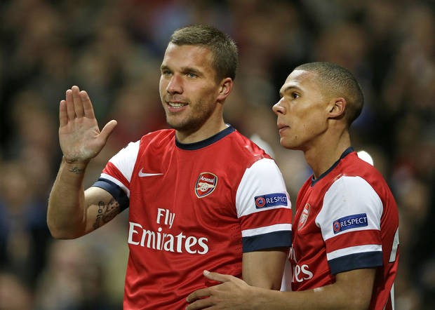 Arsenal's Lukas Podolski, left, celebrates with Kieran Gibbs after scoring his sides second goal during the Champions League Group B soccer match between Arsenal and Olympiakos at the Emirates Stadium in London, Wednesday, Oct. 3, 2012. (AP Photo/Kirsty Wigglesworth)