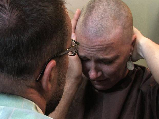 "A husband comforts his wife, a newly diagnosed cancer patient, after a stylist shaved off her thinning hair in the Oscar-nominated short documentary ""Mondays at Racine."" Photo provided. <strong></strong>"