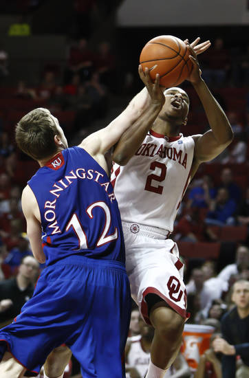 Oklahoma's Steven Pledger (2) is fouled on the way to the basket by Kansas guard Brady Morningstar (12) in the second half of a NCAA Men's College Basketball game in Norman, Okla.  on Saturday, Feb. 26, 2011.   Kansas won 82-70.  (AP Photo/Alonzo Adams)