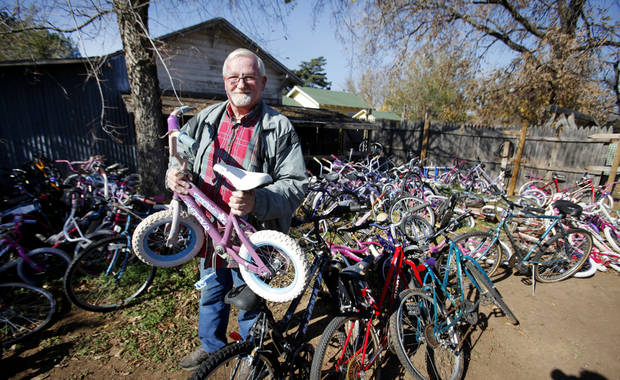 John Ballard poses with some of the bicycles he repairs to give to  underpriviliged children.  Photo By  Steve Gooch, The Oklahoman