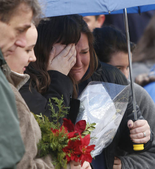 Mourners pay their respects at a memorial for shooting victims near Sandy Hook Elementary School, Sunday, Dec. 16, 2012 in Newtown, Conn.  A gunman walked into Sandy Hook Elementary School in Newtown Friday and opened fire, killing 26 people, including 20 children. (AP Photo/Jason DeCrow) ORG XMIT: CTJD110