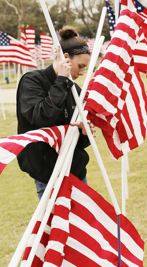Britney Lowery helps to plant American flags in honor of children who died in America in 2011 in the fields south of the state Capitol Sunday, April 7, 2013. Photo by Doug Hoke, The Oklahoman