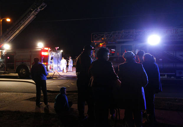 Neighbors gather around the scene of a fatal house fire near NE 20 and Bath Avenue on Tuesday night. Photo by Sarah Phipps, The Oklahoman <strong>SARAH PHIPPS</strong>