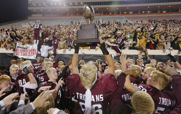 Jenks' Austin Martin (86) hoist the trophy for the Trojan fans during the Class 6A Oklahoma state championship football game between Norman North High School and Jenks High School at Boone Pickens Stadium on Friday, Nov. 30, 2012, in Stillwater, Okla.   Photo by Chris Landsberger, The Oklahoman