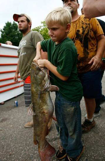 Hunter Williams (8) drags one of his families catfish to the weigh in table. Noodlers from across the state came to Bob's Pig House in Pauls Valley, Okla to weigh in their fish and compete in the 11th annual Okie Noodling tournament on Saturday July 10, 2010. Photo by Mitchell Alcala, The Oklahoman  ORG XMIT: KOD ORG XMIT: OKC1007111356210887 ORG XMIT: 1007112132192058