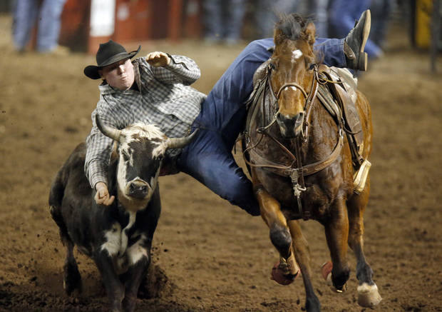 Cody Mousseau leaps from his horse during the steer wrestling event at the International Finals Rodeo at the State Fair Arena in Oklahoma City,  Saturday,Jan. 19, 2013. Photo by Sarah Phipps, The Oklahoman
