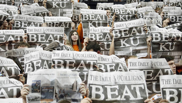 An Oklahoma State student is seen in the sea of newspaper during the college basketball game between the Oklahoma State University Cowboys (OSU) and the University of Kanas Jayhawks (KU) at Gallagher-Iba Arena on Wednesday, Feb. 20, 2013, in Stillwater, Okla. Photo by Chris Landsberger, The Oklahoman