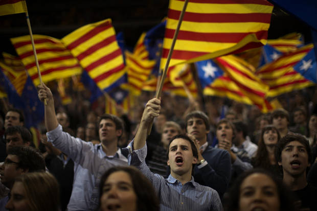 "Supporters of center-right Catalan Nationalist Coalition (CiU) leader, Artur Mas, wave their pro-independence ""estelada"" flags during the last day of campaigning in a meeting in Barcelona, Spain, Friday, Nov. 23, 2012. Catalonia holds elections on Sunday that will be seen as a test of the regional government's plans to hold a referendum on independence, and one of the key issues emerging is the theoretical place of a free Catalonia in Europe. (AP Photo/Emilio Morenatti)"
