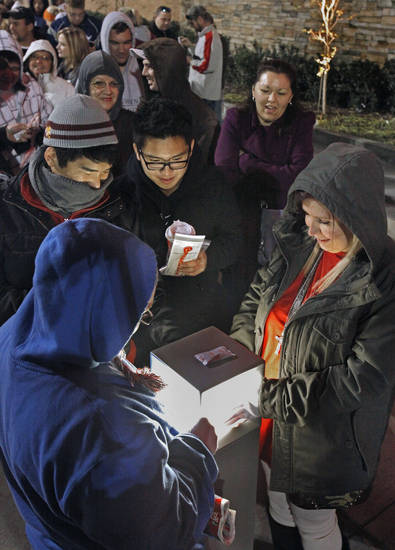 Shoppers (clockwise) Michael and John Nguyen, Jessica Handy and Stephanie Mattingley try to warm up over a light as they wait in line for Target's midnight opening on Black Friday. <strong>STEVE SISNEY - THE OKLAHOMAN</strong>