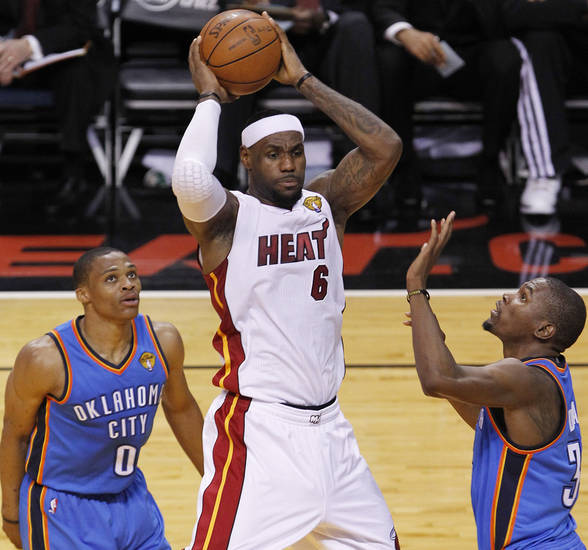 Miami Heat small forward LeBron James (6) passes between Oklahoma City Thunder point guard Russell Westbrook and Kevin Durant, during the first half at Game 3 of the NBA Finals basketball series, Sunday, June 17, 2012, in Miami. (AP Photo/Wilfredo Lee) ORG XMIT: NBA123
