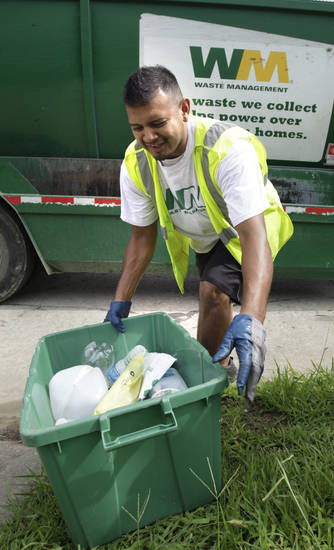 Right: Joel Ojeda with Waste Management picks up a tub of recyclables in a residential neighborhood.  OKLAHOMAN ARCHIVE PHOTO