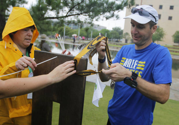 Helen Steifmiller, a museum curator, helps Ewell Condron, of Pottsboro, Texas, attach his medal to a chair at the Oklahoma City Memorial during the twelfth annual Oklahoma City Memorial Marathon in Oklahoma City, Sunday, April 29, 2012.  Photo by Garett Fisbeck, For The Oklahoman