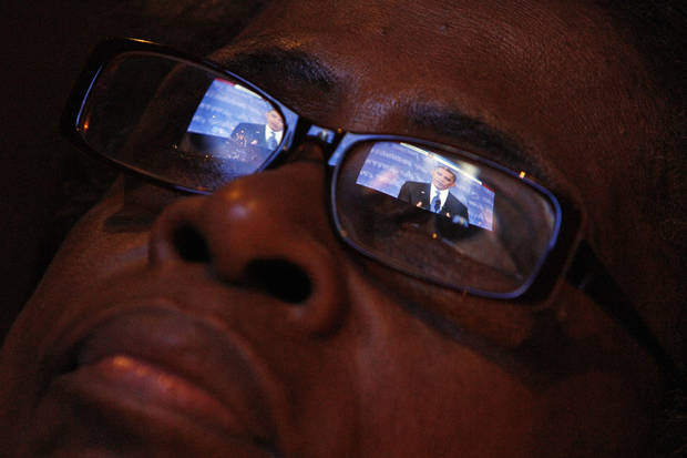 President Obama is reflected in Mary Jackson's eyeglasses as she watches the first Presidential debate between Republican presidential candidate, former Massachusetts Gov. Mitt Romney, and President Barack Obama on Wednesday Oct. 3, 2012, at a restaurant in the West Oak Lane section of Philadelphia. (AP Photo/ Joseph Kaczmarek)