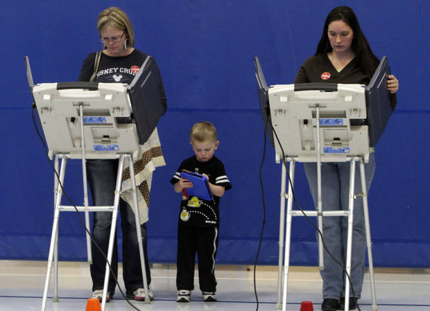 Amy Deming, left, casts her ballot as her son Max, 4, plays with his V-Reader and Wendy Watt, right, votes at Pony Express Elementary School in Eagle Mountain, Utah, Tuesday, Nov. 6, 2012. (AP Photo/The Salt Lake Tribune, Rick Egan) DESERET NEWS OUT; LOCAL TV OUT; MAGS OUT