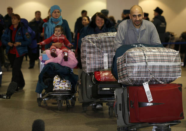 Russian-Syrian family leave passport control zone just after their arrival from Beirut in Moscow Domodedovo airport, Russia, Wednesday, Jan. 23, 2013. The Kremlin's evacuation of Russians from Syria on Tuesday marks a turning point in its view of the civil war, representing increasing doubts about Bashar Assad's hold on power and a sober understanding that it has to start rescue efforts before it becomes too late. The operation has been relatively small-scale - involving fewer than 100 people, mostly women and children - but it marks the beginning of what could soon turn into a risky and challenging operation.  (AP Photo/Alexander Zemlianichenko)