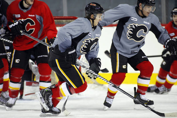 Calgary Flames' Mikael Backlund, center, from Sweden, chases the puck during training camp in Calgary,  Alberta, Monday, Jan. 14, 2013. (AP Photo/The Canadian Press, Jeff McIntosh)