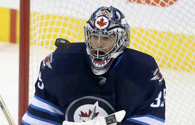 Winnipeg Jets goaltender Al Montoya (35) juggles a New Jersey Devils shot during first period NHL hockey action in Winnipeg, Manitoba, Sunday, Oct. 13, 2013. (AP Photo/The Canadian Press, Trevor Hagan)