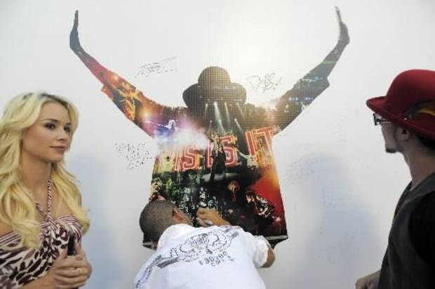 "Michael Jackson's dancers wrote on a ""This Is It"" movie poster. ((AP Photo/Jae C. Hong)"