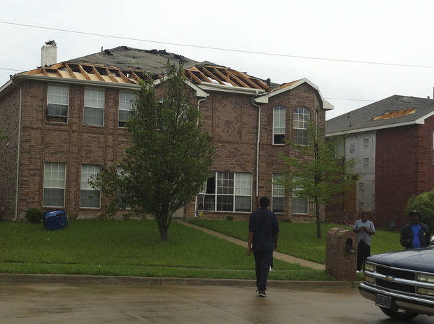 "A roof is damaged after a storm passed through in Lancaster, Texas on Tuesday, April 3, 2012.  Tornadoes tore through the Dallas area on Tuesday, tearing roofs off homes, tossing trucks into the air and leaving flattened tractor trailers strewn along highways and parking lots. The National Weather Service confirmed at least two separate ""large and extremely dangerous"" tornadoes in the Dallas-Fort Worth area. Several other developing twisters were reported as a band of violent storms moved north through the metropolitan area.   (AP Photo/The Dallas Morning News, Steve Pfost)  MANDATORY CREDIT; MAGS OUT; TV OUT; INTERNET OUT; AP MEMBERS ONLY  ORG XMIT: TXDAM106"