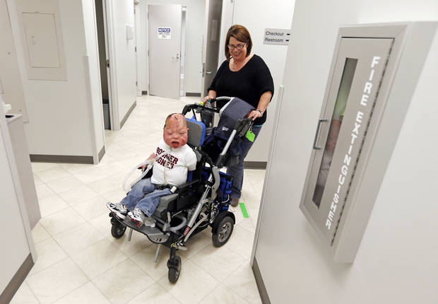 Denise Burns pushes her son, Fletcher Burns, 8, to a therapy appointment at the Children's Center in Bethany. Photo by Nate Billings, The Oklahoman <strong>NATE BILLINGS - NATE BILLINGS</strong>