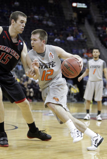 Oklahoma State's Keiton Page (12) drives past Texas Tech's Robert Lewandowski (15) during the Big 12 tournament men's basketball game between the Oklahoma State Cowboys and the Texas Tech Red Raiders at the Sprint Center, Wednesday, March, 7, 2012. Photo by Sarah Phipps, The Oklahoman