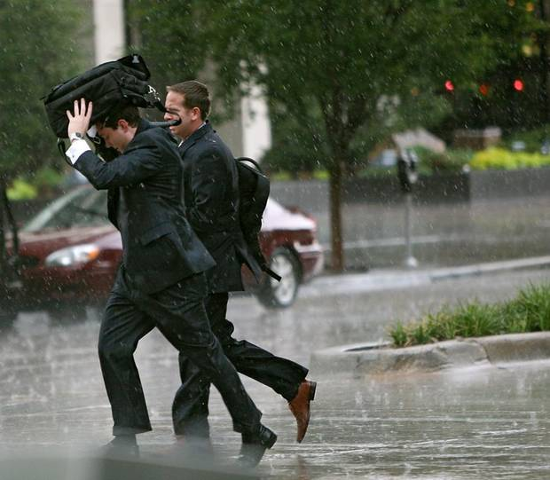 Two pedestrians try to take shelter from the rain as they run across the intersection of Main and Broadway in downtown Oklahoma City on Tuesday, July 12, 2011. Photo by John Clanton, The Oklahoman ORG XMIT: KOD