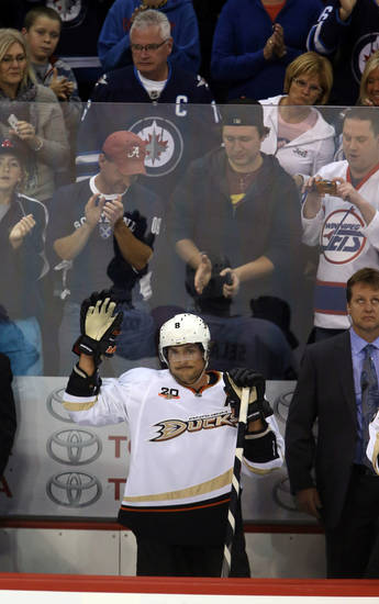 Anaheim Ducks' Teemu Selanne waves as the fans salute him during the first period against the Winnipeg Jets during NHL hockey action in Winnipeg, Manitoba, Sunday, Oct. 6, 2013. (AP Photo/The Canadian Press, Trevor Hagan)