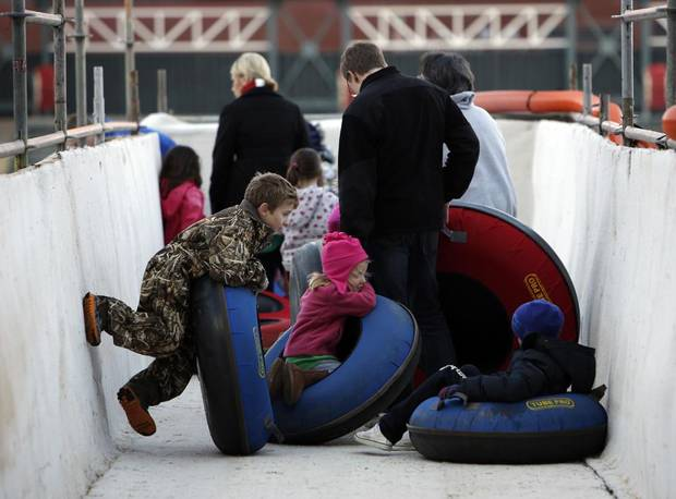 People line up to ride tubes down a snow slope at Chickasaw Bricktown Ballpark in Oklahoma City, Saturday, Nov. 24, 2012.  Photo by Garett Fisbeck, The Oklahoman