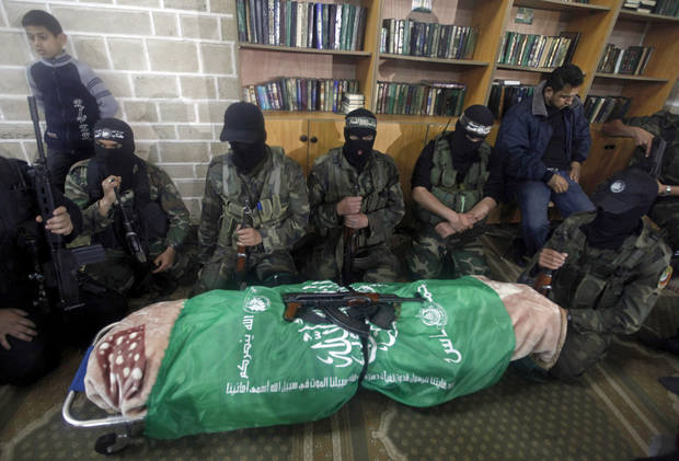 "Masked Hamas militants knell next to the flagged-draped body of Hamas member of the Palestinian Parliament Mariam Farhat, 64, who died early Sunday at the Gaza hospital in Gaza City, Sunday, March 17, 2013. Farhat, known as the ""mother of martyrs,"" lost three of her six sons, all three Hamas militants, in fighting with Israel. (AP Photo/Hatem Moussa)"
