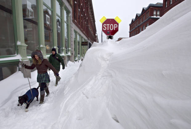 A couple walks past a large snow drift in the Old Port section of Portland, Maine, Saturday, Feb. 9, 2013.  Officials are cautioning residents to stay off the roads in Maine, where Portland set an all-time snowfall record. (AP Photo/Robert F. Bukaty) ORG XMIT: MERB108