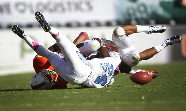 Mimai's Rashawn Scott (80) drops a pass after North Carolina players Terry Shankle (24) and Gene Robinson knocked him to the ground during the second half of a NCAA college football game in Miami, Saturday, Oct. 13, 2012. North Carolina won 18-14. (AP Photo/J Pat Carter)