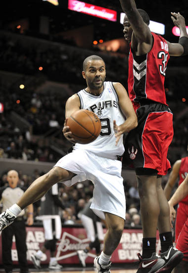 San Antonio Spurs guard Tony Parker, of France, drives against Toronto Raptors forward Ed Davis during the first half of an NBA basketball game on Wednesday, Dec. 26, 2012, in San Antonio. (AP Photo/Bahram Mark Sobhani)