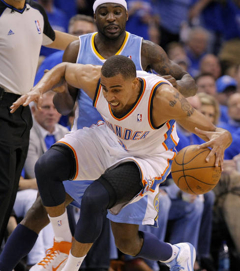 Oklahoma City's Thabo Sefolosha (2) grabs a loose ball from Denver's Ty Lawson (3) during the first round NBA playoff game between the Oklahoma City Thunder and the Denver Nuggets on Sunday, April 17, 2011, in Oklahoma City, Okla. Photo by Chris Landsberger, The Oklahoman