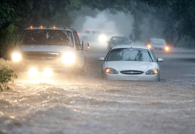 The driver of a pickup truck attempts to help a stranded motorist whose car stalled in deep floodwaters on Kelly Avenue between Hefner and 122nd in Oklahoma City, OK, Monday, June 14, 2010. By Paul Hellstern, The Oklahoman