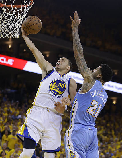Golden State Warriors' Stephen Curry (30) lays up a shot against Denver Nuggets' Wilson Chandler, right, during the second half of Game 3 in a first-round NBA basketball playoff series on Friday, April 26, 2013, in Oakland, Calif. (AP Photo/Ben Margot)