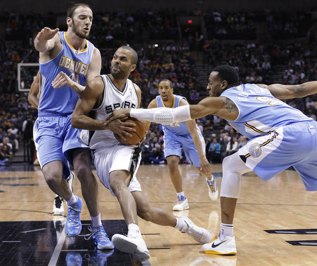 San Antonio Spurs' Tony Parker, center, of France, drives between Denver Nuggets defenders Kosta Koufos (41) and Andre Iguodala (9) during the first half of an NBA basketball game, Wednesday, March 27, 2013, in San Antonio. (AP Photo/Eric Gay)