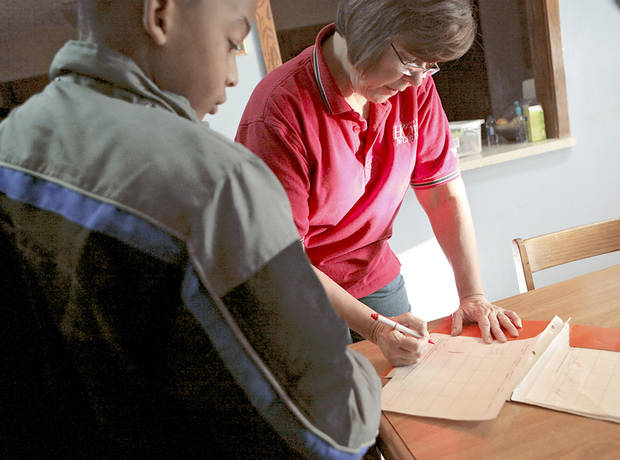 Harriet Hall, an associate house parent at Boys Ranch Town in Edmond, looks over schoolwork with a young resident. Photo by John Clanton, The Oklahoman