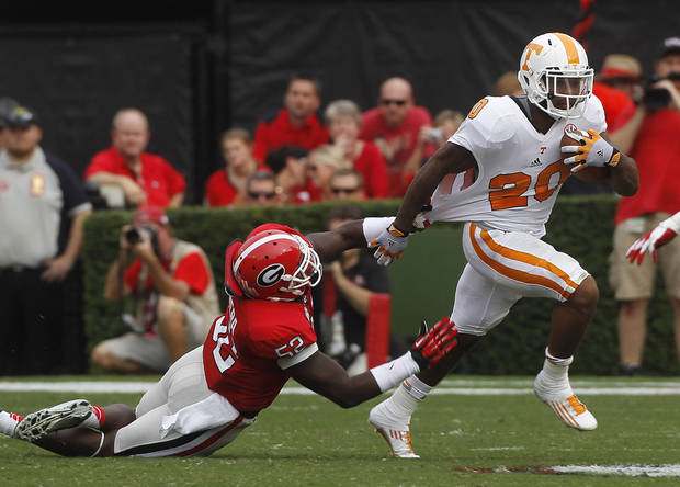 Tennessee running back Rajion Neal (20) is dragged down by Georgia linebacker Amarlo Herrera (52) during the first half of an NCAA college football game in Athens, Ga., Saturday, Sept. 29, 2012. (AP Photo/John Bazemore)