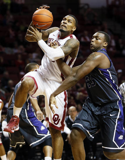 Oklahoma&#039;s Romero Osby (24) is fouled by TCU&#039;s Devonta Abron (23) on his way to the hoop during an NCAA men&#039;s basketball game between the University of Oklahoma (OU) and Texas Christian University (TCU) at the Lloyd Noble Center in Norman, Okla., Monday, Feb. 11, 2013. Photo by Nate Billings, The Oklahoman