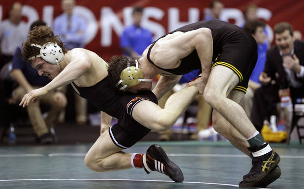 Iowa's Derek St. John, right, tries to take down Oklahoma State's Alex Dieringer during their 157-pound semifinal round match at the NCAA Division I wrestling championships on Friday, March 22, 2013, in Des Moines, Iowa. (AP Photo/Charlie Neibergall)