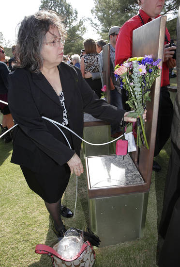 Nina Gonzales places flowers at the chair of her uncle Antonio