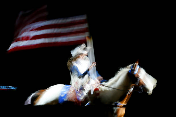 A rider carries in the American flag before the International Finals Rodeo at Jim Norick Arena at State Fair Park in Oklahoma City, Saturday, Jan. 18, 20914. Photo by Bryan Terry, The Oklahoman