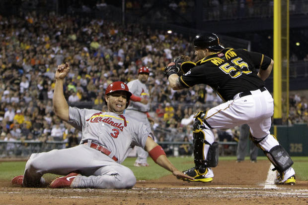 St. Louis Cardinals' Carlos Beltran (3) scores ahead of the tag by Pittsburgh Pirates catcher Russell Martin (55) on a single by Matt Holliday during the fourth inning of a baseball game in Pittsburgh on Wednesday, July 31, 2013. (AP Photo/Gene J. Puskar)