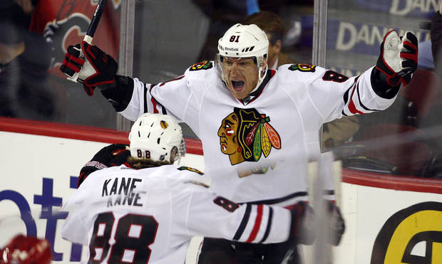 Chicago Blackhawks&#039; Marian Hossa, right, from Slovakia, celebrates his goal with teammate Patrick Kane during overtime of an NHL hockey game in Calgary, Alberta, Saturday, Feb. 2, 2013. The Blackhawks defeated the Flames 3-2 in a shootout. (AP Photo/The Canadian Press, Jeff McIntosh)
