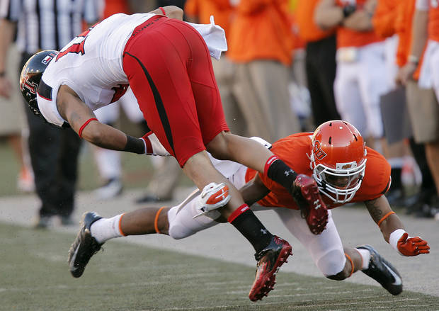 Oklahoma State's Ashton Lampkin (6) stops Texas Tech's Darrin Moore (14) during the college football game between the Oklahoma State University Cowboys (OSU) and Texas Tech University Red Raiders (TTU) at Boone Pickens Stadium on Saturday, Nov. 17, 2012, in Stillwater, Okla.   Photo by Chris Landsberger, The Oklahoman
