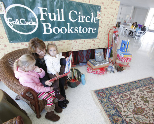 Beverly Lackey reads a book Friday to her granddaughters Kelsey Lackey, 5, left and Mallory Lackey, 2, at the Full Circle Bookstore pop-up in the Myriad Gardens.  Photo By Steve Gooch, The Oklahoman