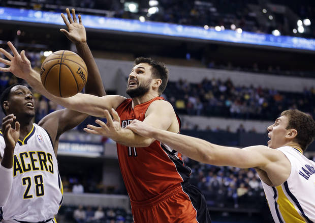 Toronto Raptors' Linas Kleiza (11) shoots under pressure from Indiana Pacers' Ian Mahinmi (28) and Tyler Hansbrough during the first half of an NBA basketball game, Tuesday, Nov. 13, 2012, in Indianapolis. (AP Photo/Darron Cummings)