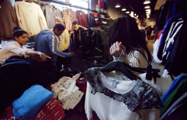 In this Wednesday, Dec. 12, 2012 photo, Lana Nguyen, right, holds clothes to try on as she shops with Lisa George, left, and friends in an H&M store, in Atlanta. The Federal Reserve reports how much consumers borrowed in December on Thursday, Feb. 7, 2013.  (AP Photo/David Goldman)