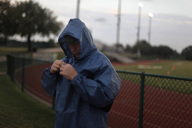 Mike Millican, of Yukon, puts his rain gear on before a high school football game between Heritage Hall and Clinton in Oklahoma City, Friday, Sept. 7, 2012.  The game was delayed due to lightning.  Photo by Garett Fisbeck, The Oklahoman