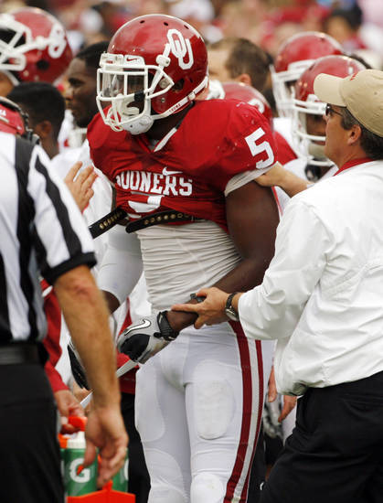 Joseph Ibiloye (5) is tended to on the sidelines after an injury during the University of Oklahoma (OU) football team's annual Red and White Game at Gaylord Family/Oklahoma Memorial Stadium on Saturday, April 14, 2012, in Norman, Okla.  Photo by Steve Sisney, The Oklahoman